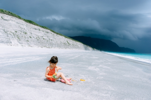 Beach play on Tokyo's Surf Island while a squall approaches, Niijima Island